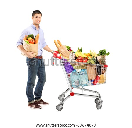Full length portrait of a man holding a shopping bag and shopping cart isolated on white background