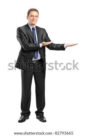 Full length portrait of a man in suit gesturing welcome isolated on white background
