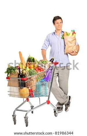Full length portrait of a man with paper bag next to a shopping cart full with groceries isolated on white background
