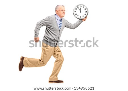 Full length portrait of a mature gentleman running and holding a clock, isolated on white background