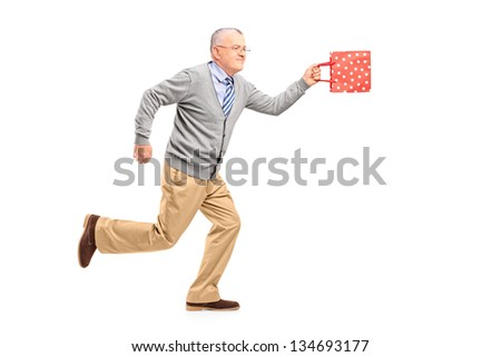 Full length portrait of a mature gentleman running with a gift bag, isolated on white background