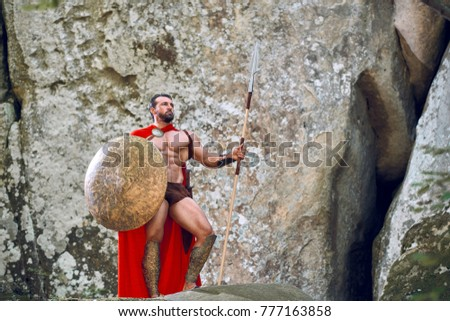 Full length portrait of a mature Spartan warrior wearing red cloak holding a spear and a shield posing outdoors thoughtfully copyspace historic costume cosplay muscles athletic brave fearless concept.