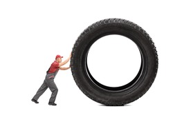 Full length portrait of a mechanic in a gray jumpsuit pushing a giant black tire isolated on white background