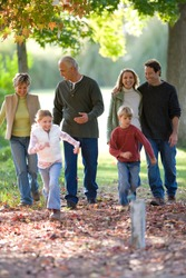 Full length portrait of a multi-generational family walking in a park with couples in embrace and children sprinting ahead during a sunny day in autumn.