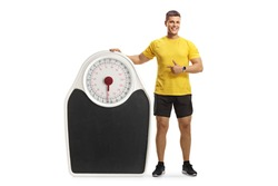 Full length portrait of a muscular man in sportswear leaning on a big scale and pointing isolated on white background