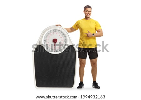 Full length portrait of a muscular man in sportswear leaning on a big scale and pointing isolated on white background Сток-фото ©