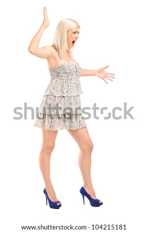 Full length portrait of a nervous blond female shouting isolated on white background