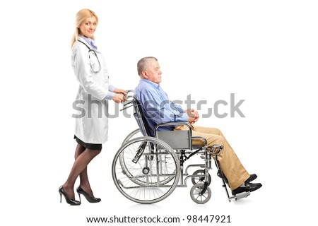 Full length portrait of a nurse or doctor pushing a handicapped senior man in a wheelchair isolated on white background - stock photo