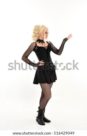 Full length portrait of a pretty blonde girl wearing a black