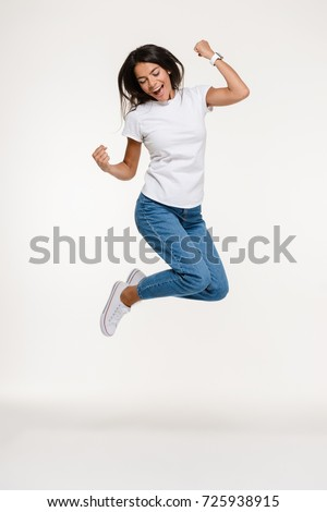 Full length portrait of a pretty joyful woman jumping isolated over white background
