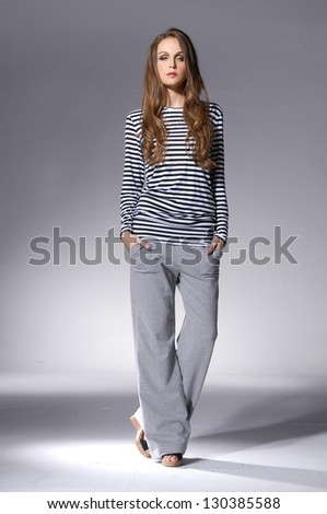 Full length portrait of a pretty young woman posing over light background