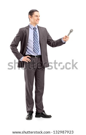 Full length portrait of a professional male reporter holding a microphone, isolated on white background