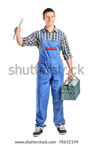 Full length portrait of a repairman in overall holding a wrench and toolbox isolated on white background