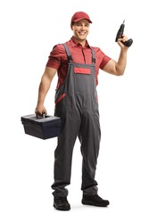 Full length portrait of a repairman with a tool box and a drill isolated on white background