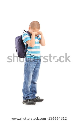 Full length portrait of a sad schoolboy crying isolated on white background