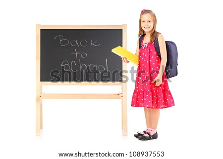Full length portrait of a schoolgirl holding a notebook and posing next to a board isolated on white background
