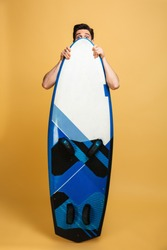 Full length portrait of a scraed young man dressed in swimsuit hiding behind a surfboard isolated over yellow background