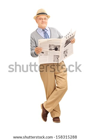 Full length portrait of a senior gentleman holding a newspaper and leaning against a wall