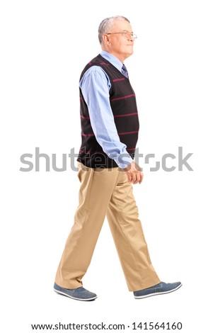 Full length portrait of a senior man walking isolated on white background