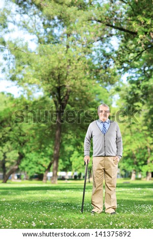 Full length portrait of a senior man walking with a cane in a park