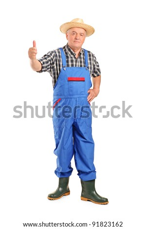 Full length portrait of a senior smiling farmer giving a thumb up isolated on white background