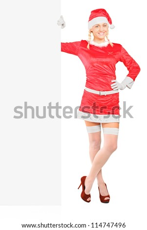 Full length portrait of a sexy female in santa costume standing next to a blank billboard