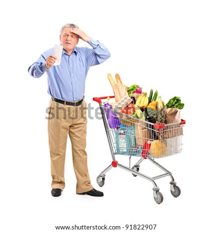 Full length portrait of a shocked senior looking at store receipt next to a shopping cart isolated on white background