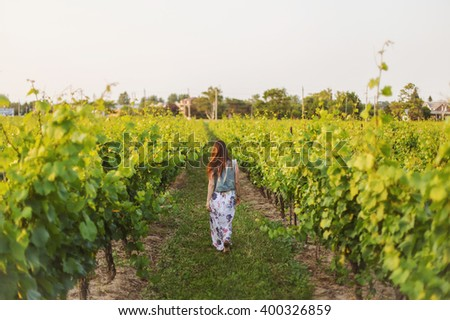 Full length portrait of a  shot from the back redhead woman in a floral print dress and denim jacket. Vineyard at sunset, copy space