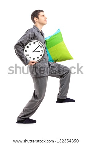 Full length portrait of a sleepwalker with a pillow and a clock isolated on white background - stock photo