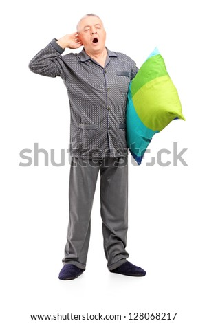 Full length portrait of a sleepy mature man in pajamas holding a pillow isolated on white background