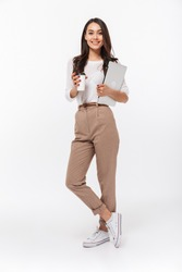 Full length portrait of a smiling asian businesswoman carrying laptop computer and cup of coffee to go while standing isolated over white background