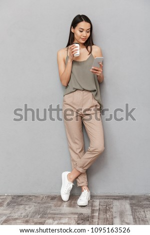 Full length portrait of a smiling asian woman holding takeaway coffee cup and using mobile phone isolated over gray background