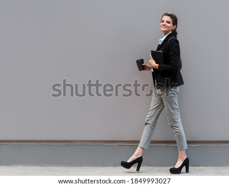 Full length portrait of a smiling businesswoman carrying notepad and cup of coffee to go while standing isolated over gray background