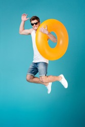 Full length portrait of a smiling cheerful man in sunglasses holding inflatable ring and jumping isolated over blue background