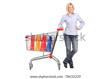 Full length portrait of a smiling female posing next to a shopping cart full with shopping bags isolated on white background