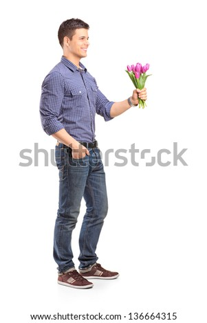 Full length portrait of a smiling guy holding flowers isolated on white background