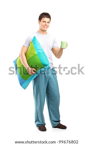 Full length portrait of a smiling male holding a pillow and cup of coffee isolated on white background