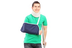 Full length portrait of a smiling male with broken arm and crutch isolated on white background