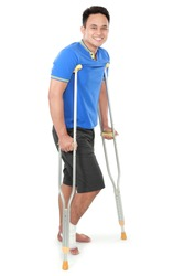 Full length portrait of a smiling male with broken foot using crutch isolated on white background