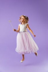 Full length portrait of a smiling pretty girl dressed in a princess dress isolated over violet background, holding magic wand, jumping