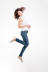 Full length portrait of a smiling pretty woman jumping isolated on a white background