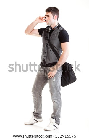 Full length portrait of a smiling school boy holding books and talking on a phone isolated on white background