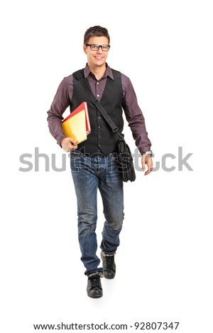 Full length portrait of a smiling school boy walking and holding books isolated on white background