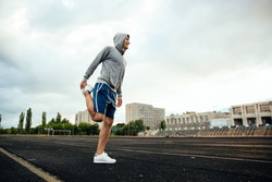 Full length portrait of a smiling sportsman doing exercises for legs, with headphones, at the stadium
