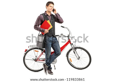 Full length portrait of a smiling student holding books and talking on a phone next to a bike isolated on white background