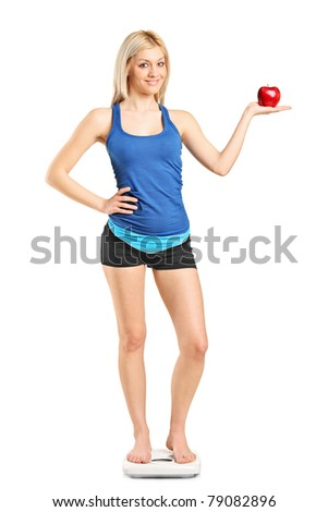 Full length portrait of a smiling woman holding a red apple and standing on a weight scale isolated on white background