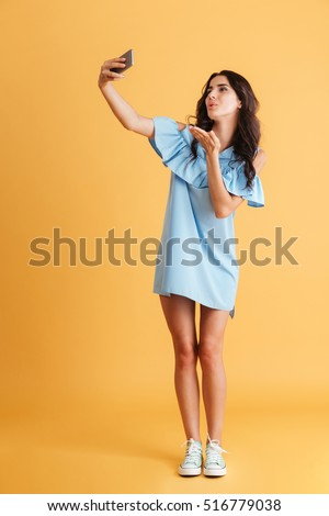 Full length portrait of a smiling woman making selfie photo on smartphone isolated on a orange background