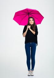 Full length portrait of a smiling woman standing under umbrella isolated on a white background