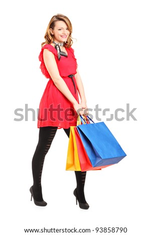 Full length portrait of a smiling young female posing with shopping bags isolated on white background