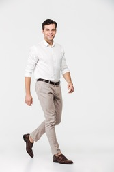 Full length portrait of a smiling young man dressed in shirt walking and looking at camera isolated over white background